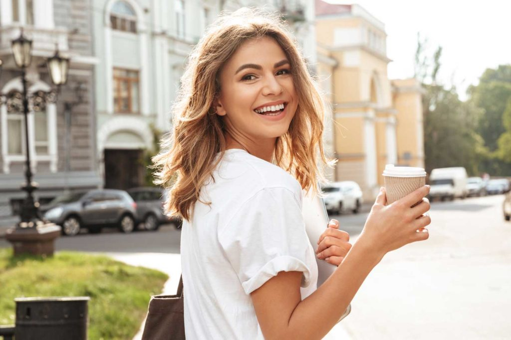 Woman smiling with a cup of coffee | Cosmetic Dentistry